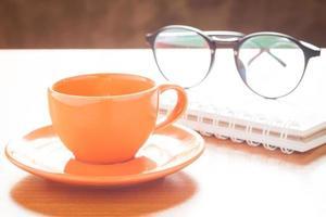 Kaffeetasse mit Notizbuch und Gläsern