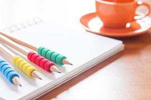Bleistifte auf einem Notizbuch mit einer Kaffeetasse auf einem Schreibtisch foto