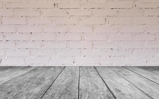 grauer Holztisch gegen eine weiße Backsteinmauer foto