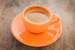 Nahaufnahme des heißen Kaffees in einer orange Tasse auf einem Holztisch