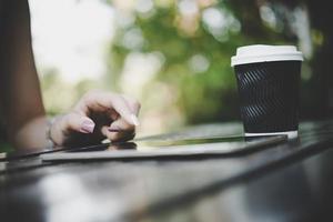 Nahaufnahme der Frau, die einen Tablet-Computer auf einem Holztisch berührt