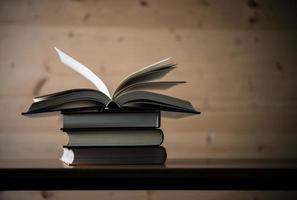 Stapel offener Bücher auf einem Holztisch foto