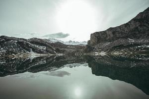 Gebirgszug, der sich in einem zugefrorenen See spiegelt