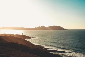 super heller Sonnenuntergang über einem Leuchtturm foto