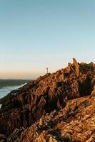 weißer Leuchtturm über riesigen riskanten Felsen foto