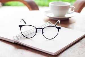 Öffnen Sie das Notizbuch und die Brille mit einer Tasse Kaffee