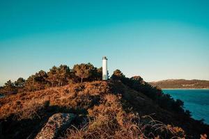 bunter weißer und blauer Leuchtturm an der Küste Spaniens