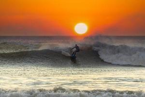 Mann, der bei Sonnenuntergang surft foto