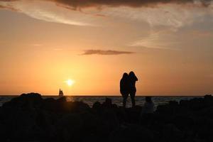 Schattenbild von zwei Personen, die auf felsigem Ufer während Sonnenuntergang stehen