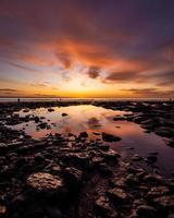 felsiges Ufer unter orange Sonnenuntergang foto