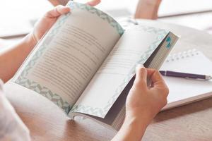 Nahaufnahme der Hände, die ein Buch in einem Café halten foto