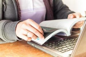 Frau liest ein Buch an einem Arbeitsplatz