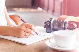 Frau, die in einem Notizbuch mit einer Kamera und Kaffee auf einem Tisch schreibt