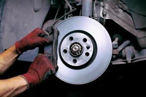 ein Mechaniker, der einen Bremsbelag wechselt