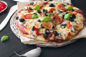 Pizza mit Tomaten, Pilzen, Oliven und Paprika foto
