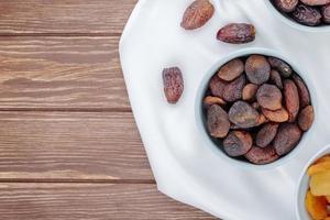 Draufsicht auf getrocknete Aprikosen in einer Schüssel und mit getrockneten Datteln