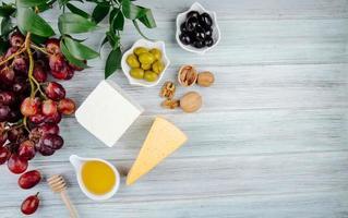 Draufsicht von verschiedenen Käsesorten mit Früchten, Nüssen, Honig und Oliven auf einem grauen hölzernen Hintergrund mit Kopienraum