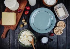 Draufsicht des Käses mit Tomaten und einer leeren Platte auf einem dunklen hölzernen Hintergrund