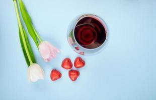 Tulpenblumen mit verstreuten herzförmigen Bonbons und einem Glas Wein auf blauem Hintergrund