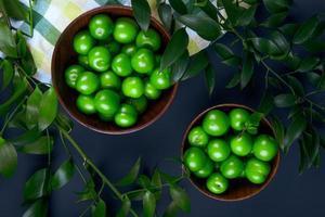 Draufsicht der grünen Pflaumen in den hölzernen Schalen auf einem schwarzen Hintergrund foto
