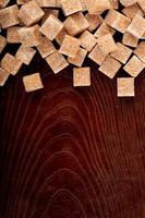braune Zuckerwürfel auf einem hölzernen Hintergrund mit Kopienraum foto