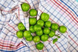 saure grüne Pflaumen auf kariertem Stoff verstreut foto