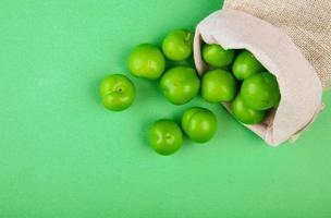 grüne saure Pflaumen in einem Sack auf einem grünen Hintergrund foto
