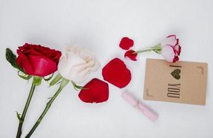 Draufsicht von roten und weißen Rosen mit einer kleinen Postkarte auf einem weißen Hintergrund foto