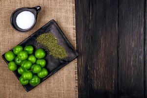 Draufsicht auf grüne Pflaumen mit getrockneter Pfefferminze auf einem schwarzen Tablett