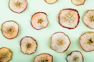 Draufsicht von getrockneten Apfelscheiben auf hellgrünem Hintergrund