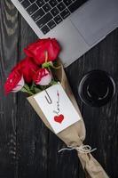 Draufsicht ein Blumenstrauß mit einer Karte, die nahe einem Laptop liegt