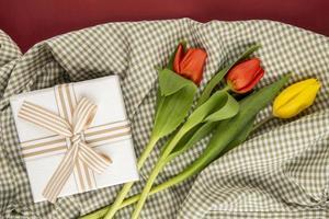 Draufsicht auf rote und gelbe Tulpen mit einem Geschenk auf kariertem Stoff
