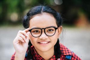 Porträt eines jungen Mädchens, das Brille hält und Kamera betrachtet