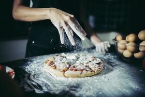 Kochhände gießen Mehl auf rohen Teig