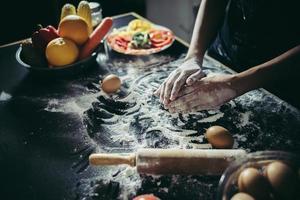 Frau knetet Teig für Pizza