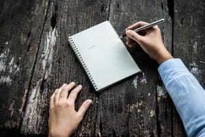 Frau, die in Notizbuch schreibt foto