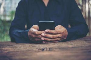 Person, die Smartphone an einem Tisch hält