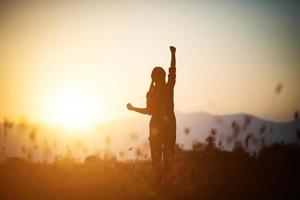 Silhouette einer Frau, die über einem schönen Himmelhintergrund betet