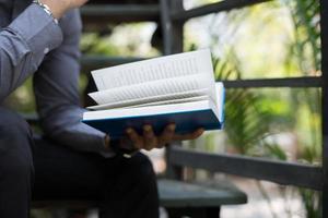 junger Mann, der Bücher im Hausgarten mit Natur liest foto