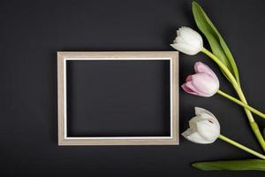 Draufsicht auf einen leeren Bilderrahmen und Tulpen foto