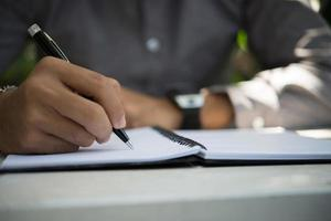 Mann, der auf Notizblock schreibt, während er im Hausgarten entspannt sitzt