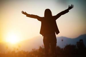 Silhouette einer Frau, die über schönen Himmelhintergrund betet