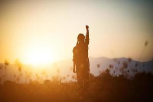 Silhouette einer Frau, die über einem Himmelhintergrund betet