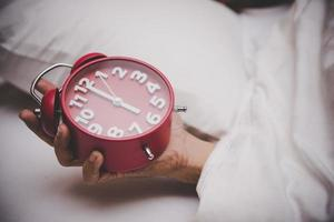 Hand im Bett den Wecker auf 6 Uhr stellen