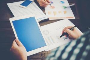 Geschäftsleute, die Tablets und Grafiken bei Besprechungen verwenden