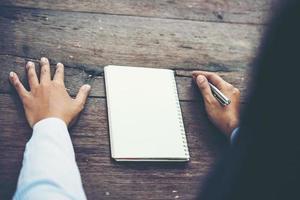 Mann, der auf leerem Notizbuch auf Holztisch schreibt