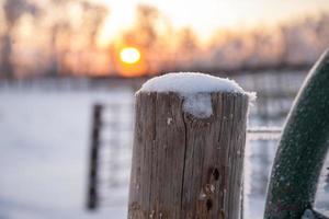 Schnee auf einem Pfosten bei Sonnenaufgang