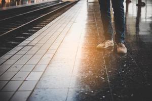 Füße eines jungen Mannes in Jeans, der auf den Zug wartet
