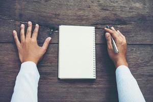 Mann, der auf leerem Notizbuch auf Holztisch schreibt foto