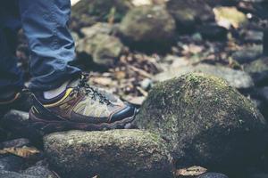 Nahaufnahme der Füße eines Mannes, die auf einem Bergweg wandern